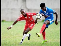 UWI's Rochane Smith (left) stays close to Portmore United's Donnegy Fer in their Red Stripe Premier League encounter at the Spanish Town Prison Oval on Sunday, January 13, 2019. UWI won the game  2-1.