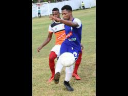 Donavan Brown (right) of Reno and Narado Brown of Dunbeholden go for the ball during a Red Stripe Premier League match between Dunbeholden and Reno yesterday at the Royal Lakes Sports Complex, in St Catherine.
