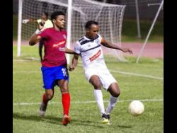 Dunbeholden's Adrian Williams  with  Cavalier's Nicholas Hamilton  in their  Red Stripe Premier League encounter at Stadium East on Sunday, December 16,2018.