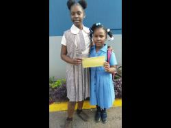 Gabrielle Gibson (left) hands over the money she saved to Brittannia Jones.