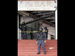 Officers with the State Police of Guerrero and Municipal Police of Acapulco guard an area near a popular bar where gunmen killed and wounded multiple people in Acapulco, Mexico, yesterday.