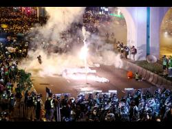 Protesters are engulfed by tear gas during a confrontation with riot police in Hong Kong on Sunday.