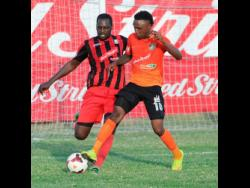 Tivoli Gardens' Jermaine 'Teddy' Johnson (right) engages in a tussle for the ball with former Arnett Gardens' captain Oneil Thompson at the Edward Seaga Sports Complex on April 12, 2016.