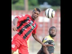 FILE Andre Clennon, formerly of Arnett Gardens, wins a header over Ramone McGregor of Barbican in a Red Stripe Premier League match on January 18, 2015.