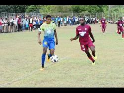 Ronaldo Webster of St Elizabeth Technical High school (left) attempts to dribble away from Newell High Schools defender Kristoff Thomas in a ISSA/WATA daCosta Cup first-round match last year.