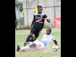 Emelio Russeau (right) of Portmore United puts in a sliding challenge on Chevone Marsh of Cavalier during a Red Stripe Premier League match on Sunday, February 10, 2019.