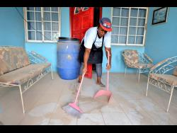 Sharon Lindsay sweeps dust from the balcony of her house in Majesty Gardens, St Andrew, yesterday.