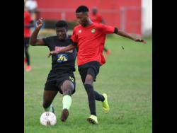 Jermaine Reid (left) of Molynes United makes a challenge on  Lime Hall player Shaquill Wallace  in the JFF Premier league play-off at the  Constant Spring playing field on Sunday, June 2,2019.