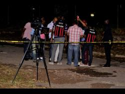 Police personnel at the scene of yesterday's triple murder in Temple Hall, St Andrew.