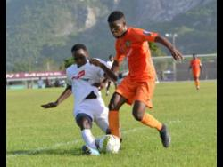 UWI FC's Andre Humphrey (right) tackles Junior McGregor of  Tivoli Garden in their Red Stripe Premier League opener yesterday.