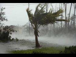 A road is flooded during the passing of Hurricane Dorian in Freeport, Grand Bahama, Bahamas, yesterday. Hurricane Dorian hovered over The Bahamas on Monday, pummeling the islands with a fearsome Category 4 assault that forced even rescue crews to take shelter until the onslaught passes. (AP Photo/Tim Aylen)