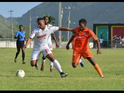 UWI FC player Michael Heaven (left) tries to get away from Tivoli Gardens' Stephen Barnett during their Red Stripe Premier League match at the UWI Mona Bowl on Sunday.