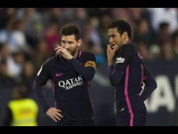 FILE Lionel Messi (left) and Neymar gesture during their match against CF Malaga in the Spanish La Liga on Saturday, April 8, 2017.