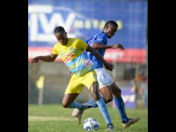 Stephen Williams (left) of Waterhouse FC shields the ball from Anjay Gayle of Vere United during their Red Stripe Premier League encounter at the Waterhouse Stadium yesterday. Waterhouse won the match 2-0.