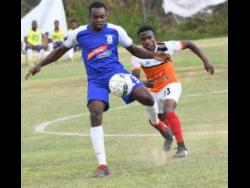 Rondell Morris (left) of Reno and Nickoy Christian of Dunbeholden vie for the ball during their Red Stripe Premier League match on Sunday, March 10, 2019.