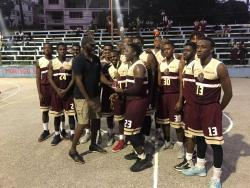 Elfraito Remekie, Jamaica Basketball coordinator, handing over  the championship trophy to members of the  Herbert Morrison Technical High School Under-19 team at the Montego Bay Cricket Club Court yesterday. Herbert Morrison won 74-58 over York Castle.