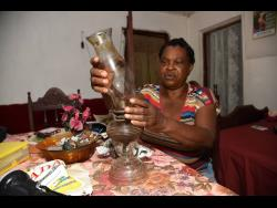 Rebecca Caballera, a resident of British in Clarendon, could soon bid her Home Sweet Home lamp goodbye as a solar project is set to take electricity to her community for the first time at last.