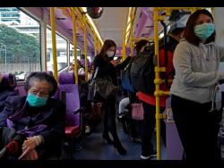 People wear protective face masks on a bus in Hong Kong on Tuesday. Hong Kong reported its first death from coronavirus, a man who had travelled from the mainland city of Wuhan that has been the epicentre of the outbreak.