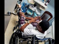Selector Bishop Escobar sits in a wheelchair in the hospital awaiting medical attention.