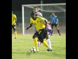 Jamaica's Jourdain Fletcher (front)  getting away from Bermuda's Reginald Lamb during the international friendly match at the Montego Bay  Sports Complex on Wednesday, March 11. Jamaica won 2-0.