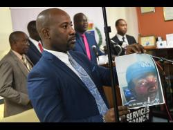 Dennis Brooks, senior communications strategist of the Jamaica Constabulary Force, shows a photo of a person of interest in the disappearance of the UWI student Jasmine Deen.