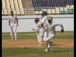 Bowler Patrick Harty (left) looks on during recent cricket action between the Jamaica Scorpions and Leeward Islands Hurricanes at the Trelawny Multipurpose Stadium.