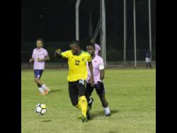 Jamaica forward Kemar Beckford (front) chases after the ball while being harried by Bermuda player Cecoy Robinson during their international friendly match at the Montego Bay Sports Complex on Wednesday, March 11.