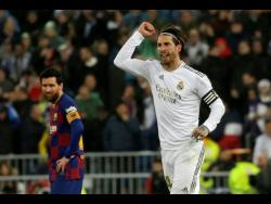 Real Madrid's Sergio Ramos celebrates as he runs past Barcelona's Lionel Messi during the Spanish La Liga match between Real Madrid and Barcelona at the Santiago Bernabeu stadium in Madrid, Spain, Sunday, March 1, 2020.