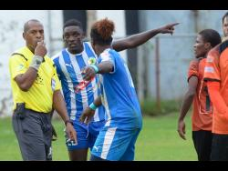 file Two Mount Pleasant players challenge a call made by referee Karl Tyrell (left) during a Red Stripe Premier League match in 2018.