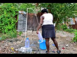 A Denham Town, Kingston, resident catches water at an outdoor pipe. Inner-city residents say the absence of amenities such as piped water is one of the main reasons they cannot stay indoors, despite the imposition of curfews to contain the spread of the novel coronavirus.