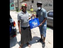Audrey Robinson of Waterhouse receiving a care package from Waterhouse FC star player Tremaine Stewart.