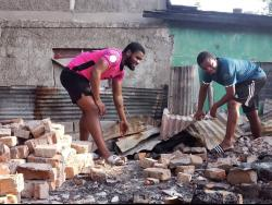 Marcel Gayle (right), head coach of Waterhouse FC, helps his player Akeem Chambers (left) clear rubble from the site where his house once stood, as fire destroyed the young footballer's home on Saturday.