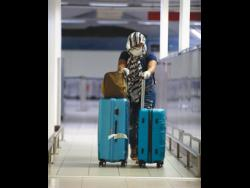 One of the Jamaicans who was stranded in the United Kingdom for weeks makes her way through the Norman Manley International Airport in Kingston yesterday.