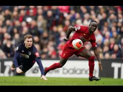 Liverpool's Sadio Mane (right) dribbles past Bournemouth's Jack Stacey during their English Premier League match at Anfield in Liverpool, England, on Saturday, March 7, 2020.