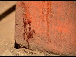 A blood-stained wall shows the spot where 15-year-old Norville Hall fell after he was attacked on Sunday.