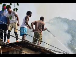 Residents of Rum Lane in Kingston try their best to put out a fire that broke out in their community yesterday.