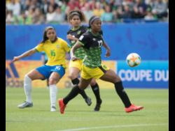Allyson Swaby (right) makes a pass ahead of teammate Marlo Sweatman (centre) and Beatriz Zaneratto Joao of Brazil during Jamaica's FIFA Women's World Cup match against Brazil at the Stade des Alpes in Grenoble, France, on Sunday, June 9, 2019.
