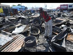 This man sifts through the rubble of the latest fire at Rae Rae Market early Tuesday morning.