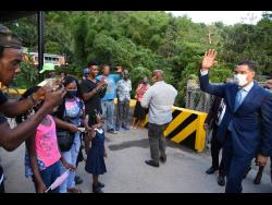 Prime Minister Andrew Holness waves to residents of Bowden Hill shortly after the opening of the Bowden Hill Bridge on Thursday.