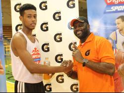 Jordan Kellier is being congratulated by Mitchell Watson, marketing manager of Pepsi Cola Jamaica, during the Gatorade/Digicel Sportsmax Jump Start Basketball clinic at the National Indoor Sports Centre.