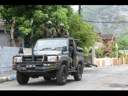 Soldiers on patrol in August Town yesterday after a  Zone of Special Operations (ZOSO) was declared in the community.