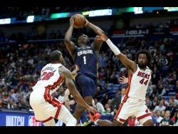 In this March 6, 2020, file photo, New Orleans Pelicans forward Zion Williamson (1) goes up for a basket as Miami Heat guard Andre Iguodala (28) and forward Solomon Hill (44) defend during the second half of an NBA basketball game in New Orleans.