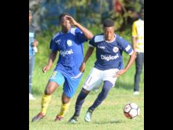 Norman Campbell of Jamaica College (right) dribbles away from Hydel High School defender Kevin Johnson during their ISSA/Digicel Manning Cup encounter on Saturday, September 29, 2018.