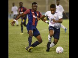 St Andrew Technical High School's Mikel Riley (left) tracks the run of Jamaica College's Rajae Lawrence  during the ISSA/Digicel Manning Cup football final at the National Stadium on Friday, November 29, 2019.