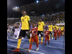FILE Damion Lowe (left) leads the Reggae Boyz on to the field at the National Stadium last year to take on Honduras in their opening Concacaf Gold Cup match.