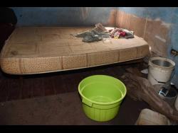 A bath pan and a bucket positioned in the house to catch rainwater from the leaking roof.