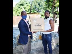 Staff sergeant Kaniel Cole (left) hands over food supplies to Jermaine Williams, a neighbour of Buckige.