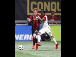 Atlanta United defender Julian Gressel battles DC United's Jamaican midfielder Oniel Fisher (right) in the first half of a Major League Soccer game at the Mercedes-Benz Stadium in Atlanta, Georgia on Sunday, March 11, 2018.