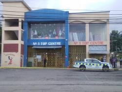 Police from the Sandy Bay Police Station process the scene of a robbery at the No 1 Top Centre in Hopewell, Hanover, yesterday after gunmen made off with about $1 million in cash.