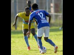 FILE Waterhouse's Mark Miller (left)  watches closely as Xahane Reid of Vere United dribbles forward during their Red Stripe Premier League encounter at the Waterhouse Stadium on Thursday, September 12, 2019.
